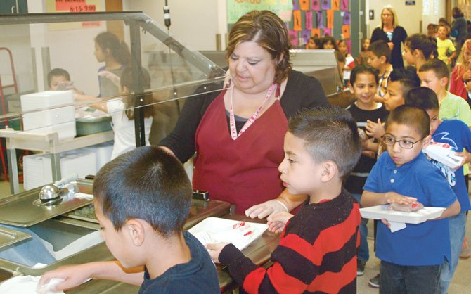 Ready to serve the more than 600 Pioneer Elementary School children arriving for lunch is Pioneer Elementary School head cook Lita Gonzalez.  Yesterday's, Wednesday, menu included chicken teriyaki and brown rice with salad, milk and a banana.