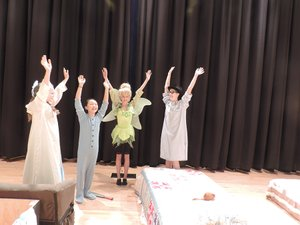 """""""This give us confidence!"""" Gaby Wilson (Tinkerbell), center, says as she and fellow actors lift arms and stretch moments before curtain Thursday. With her, from left, are Lauren Church as Wendy, Khloe Systma as Michael, and Alexandra Buckles as John."""