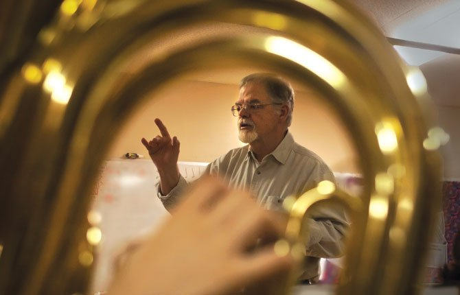 VIEWED THROUGH  a horn, Greg Weast directs St. Mary's Academy band students. Weast has decided to retire after 26 years as the school's volunteer band instructor.