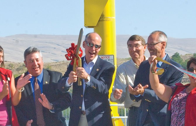 GREG WALDEN, center, wields the golden scissors at the dedication of the Union Street marine terminal during its dedication in 2012.	Chronicle file photo