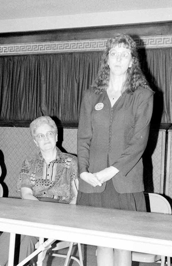 Standing, Sharon Cox (D) of Grangeville  speaks at a candidates forum in Grangeville held in October 1996. Cox was running for Idaho County Treasurer. Her Republican opponent, Donna Perrine, is seated next to her. Cox won the race that November.