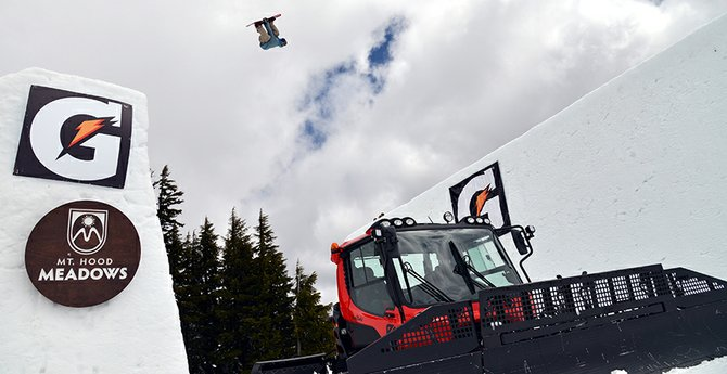 Craziness: An unidentified snowboarder is pictured upside down about 50 feet in the air over a snow cat while doing a triple backflip Sunday at Mt. Hood Meadows during SNOWBOARDING Magazine's Superpark 18 event.