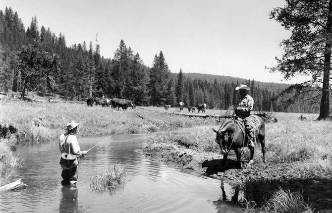 A RANCHER, HIS cattle ranged behind him, chats with a fly fisherman from the back of his horse in this historical photo. The U.S. Forest Service was started in 1906 to manage grazing issues in national forests, but its mandate has broadened to include forest management related to a wide range of forest interests.