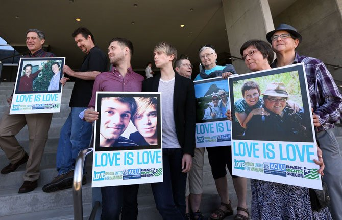 Supporters of same-sex marriage hold photos of themselves and their family members or partners on the steps of the Wayne L Morse U.S. Courthouse May 14 in Eugene. A federal judge will hear arguments Wednesday about whether a national group can defend Oregon's ban on same-sex marriage because the state's attorney general has refused to do so.