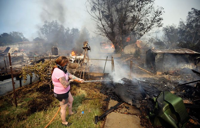 A WOMAN douses water from a hose around her home as her neighbor's home burns during a wildfire May 15 in Escondido, Calif. One of the nine fires burning in San Diego County suddenly flared Thursday afternoon and burned close to homes, trigging thousands of new evacuation orders.