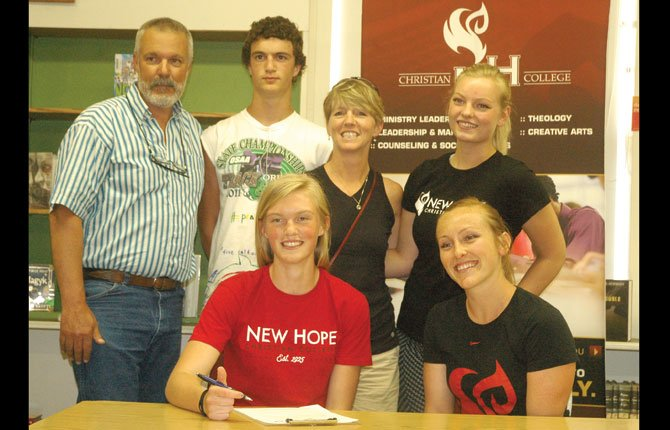 ZOE MORELLI (in red) is surrounded by loved ones and her new coaches, as she signs entrance papers for New Hope Christian College in a ceremony Thursday. In the photo are (pictured from left to right), Tim Morelli, Loreto Morelli, Sara Morelli, assistant coach Audrey Smith and head coach Anna Barton.