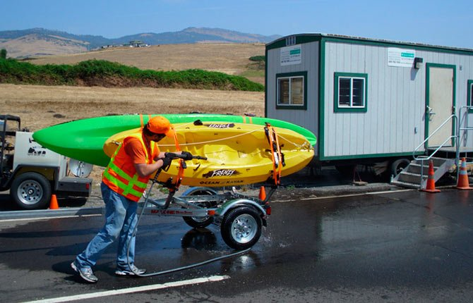 An ODFW technician at the Central Point inspection station flushes a kayak that had recently been in Lake Mead, Nevada. Lake Mead is infested with quagga mussels.