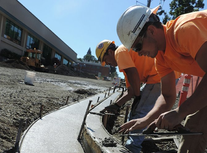 Concrete workers Shay Smith and Leo Marquez of Schuepbach Construction smooth newly poured concrete Monday at State and Fourth streets after removing half-inch spacers that kept the forming boards at the proper width during setting.