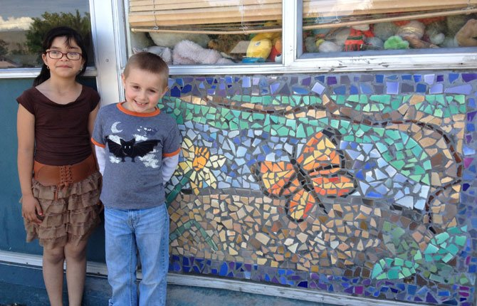 Jazmine Martinez (left) and Cayden Whitaker, Chenowith Elementary School students, smile for a photo beside one of the six mosaics installed at the front of the school on May 16, whose designs were inspired by each grade's favorite aspects of the local community. Every student had the opportunity to participate in this year's project, Tina Cramer said, and she hopes new mosaics will  continue to be added on each year.	  Contributed Photo