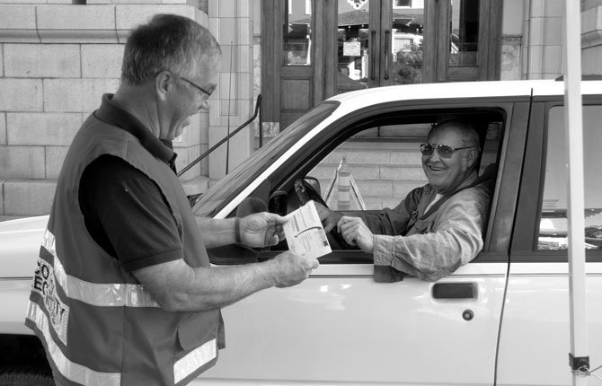 ROTARIAN Dan Boldt, left, collects a ballot from voter Don Cox this morning. Rotary members will be on the job in front of the Wasco County Courthouse, making voting easier until the 8 p.m. closing.