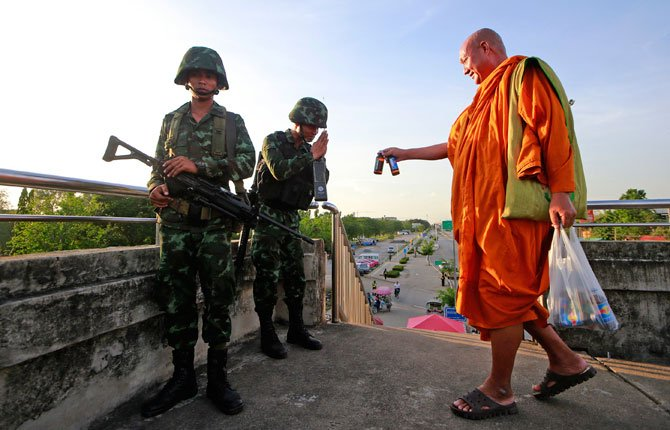 A Buddhist monk offers energy drink to Thai soldiers guarding a pedestrian overfly near the site where pro-government demonstrators stage a rally on the outskirts of Bangkok, Thailand Tuesday, May 20.
