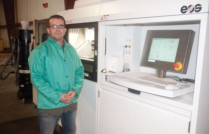 KEVIN PERRY poses near the control station on a direct metal laser sintering machine, which metal powder and lasers to create metal parts layer by layer.