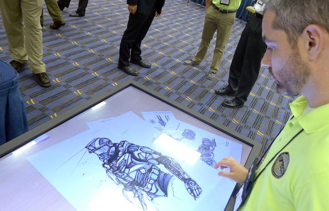Michael Fieldson , the civilian project manager for the Tactical Assault Light Operator Suit at McDill Air Force Base, looks at sketches of the body armor exoskeleton during the Special Operations Forces Industry Conference in Tampa, Fla. on May 20. Elite US special operations forces may be a few short years away from donning a similar suit.
