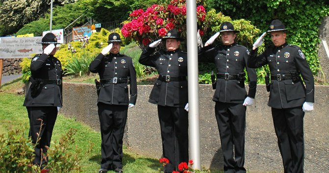 The Skamania County Sheriff's Honor Guard salute the flag lowered to half-staff at a ceremony for Peace Officer Memorial Day on May 15. A total of 14 officers from around the Columbia River Gorge who lost their lives in the line of duty over the years were commemorated during the ceremony. A bell was rung for each of the 14 officers who have died in the line of duty throughout the Columbia River Gorge over the years.