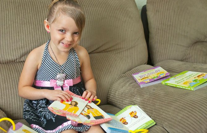 Aleah Edmondson, 4, pictured with her books, struggles with a hearing impairment and was the recipient of funds and educational materials raised by the 2013 Columbia Gorge ESD's Rainy Day Fund Run.