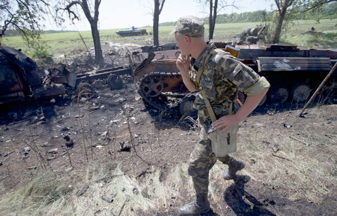 An Ukrainian soldier walks past charred APCs at a gunfight site near the village of Blahodatne, eastern Ukraine, on Thursday, May 22, 2014. At least 11 Ukrainian troops were killed and about 30 others were wounded when Pro-Russians attacked a military checkpoint, the deadliest raid in the weeks of fighting in eastern Ukraine. Three charred Ukrainian armored infantry vehicles, their turrets blown away by powerful explosions, and several burned vehicles stood at the site of the combat.
