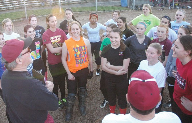 MEMBERS OF The Dalles softball gather around coach Steve Garrett (bottom left) during a recent practice at 16th Street Ballpark. The Tribe had four players pick up all-conference recognition, led by first-teamer Morgan Triperinas and second-team mates Morgan Goslin, Maddy Bradford and Ruthie Ford.                         			  TDC File photo