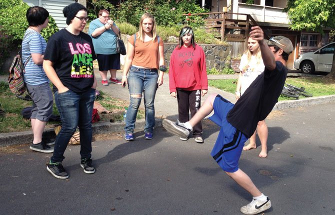 TEENS GATHER in the street and parking area on West 11th Street near The Dalles High School where a conflict between teens and residents ended in citations Wednesday.Contributed photo