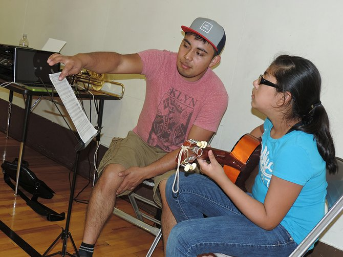 LA BANDA teacher Bruno Vargas talks chords with Sarah Santillan, 13, of Parkdale, last week during a lesson at Pine Grove School.