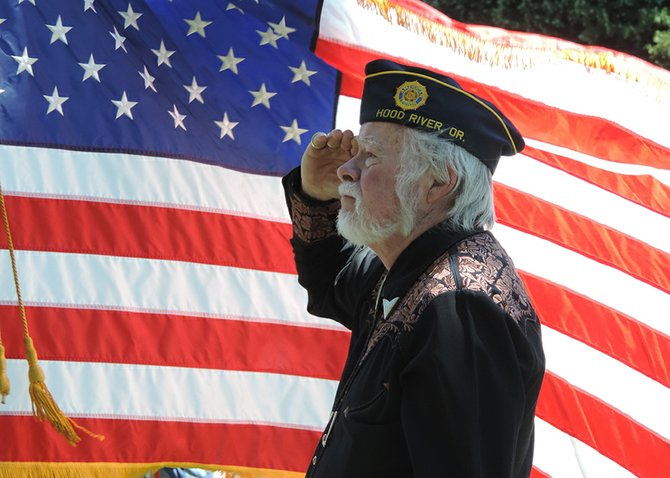 Veteran Bob Losli salutes the flag during the opening Monday's ceremony at Idlewilde Cemetery.