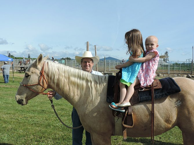 Lila May Schow, 3, right, and her sister, Mia, enjoy a ride Saturday at Hood River County Fairgrounds. Craig Ortega, left, saddled up Barbie so that the girls could enjoy the experience.