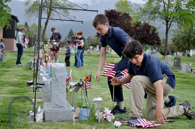Despite stormy skies, scouts with Grangeville Troop 555 were out in force last Friday, May 23, placing American flags, and replacing worn out ones, at the graves of veterans buried at Prairie View Cemetery.