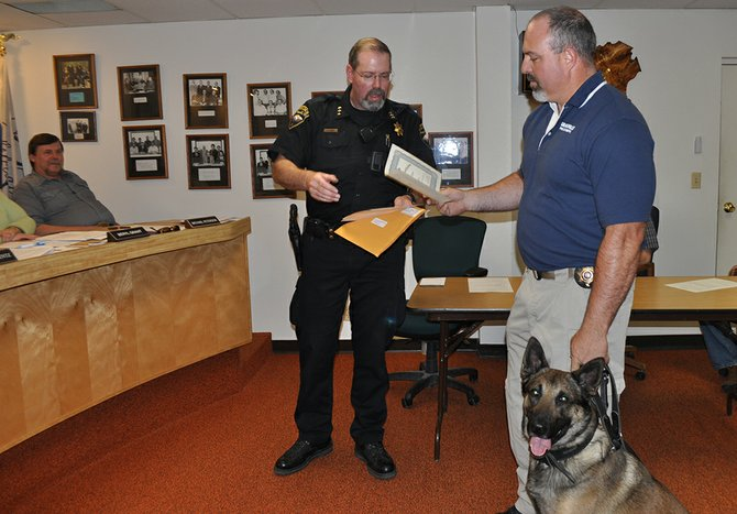 Grangeville Police Officer Wes Walters (right) and his dog, Taser, are presented a certificate by GPD Chief Morgan Drew for completing 80 hours of controlled substance canine training through the Idaho POST Academy.