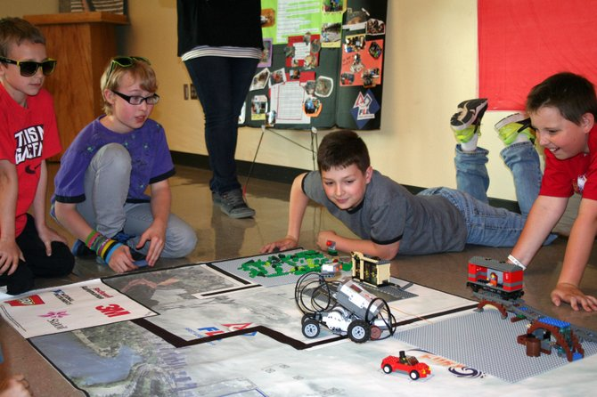 "DUFUR tech program participants watch in anticipation as the robotic lego car they built and programmed together attempts to complete one of its assigned missions at the May 19 ""Battle of the Bots"" held at Dufur School. Contributed photo"