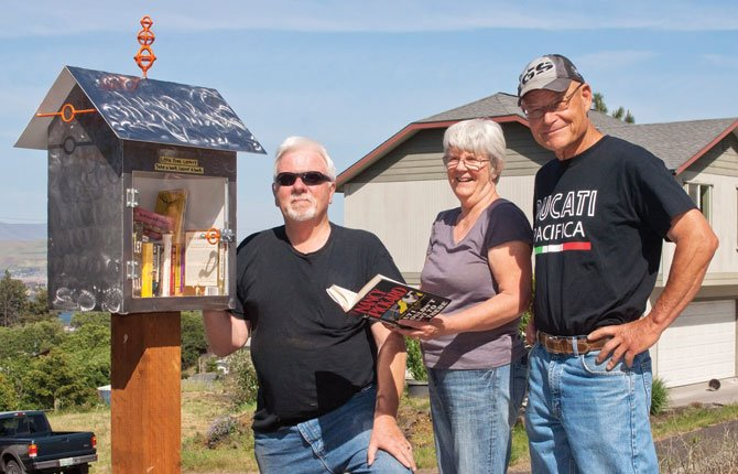 "Ron Carpenter, right, shows off a shiny new ""Little Free Library"" to neighbors Katy and John. He recently installed the little book exchange along West Scenic Drive in The Dalles, and hopes the community at large will make use of it."