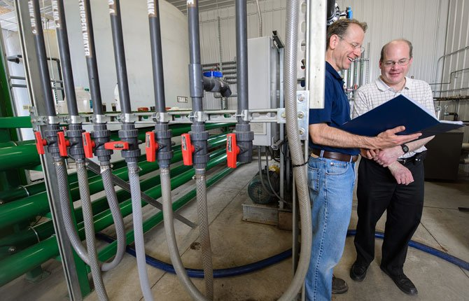 Jim Wallace and Steven Safferman are shown at a dairy farm where they have helped to convert manure into clean water. A technology for extracting drinkable water from manure is on its way to commercial application this year, Michigan State University said May 29.