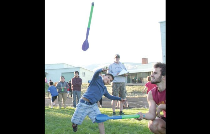 FORMER THE DALLES track and field standout Luke Conklin, assists a young boy during the javelin toss event at the District 21 Elementary School Meet at Wahtonka. In all,  55 athletes attended. Coordinator Tom Conklin, uses such platforms to get youths active and in a sports program.