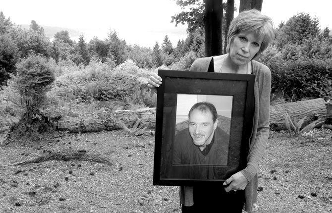 Connie OlberG poses for a photo in the backyard of her home May 21 in Sammamish, Wash., She holds a photo of her brother, Donald Douglass, a U.S. Army veteran, who had a small spot on his forehead diagnosed as cancerous at the Seattle Veterans Affairs hospital in 2011. According to his lawyer, the hospital's delay in removing it contributed to his death in 2012, a case that mirrors concerns being raised nationally about the Veteran Affairs health care system.
