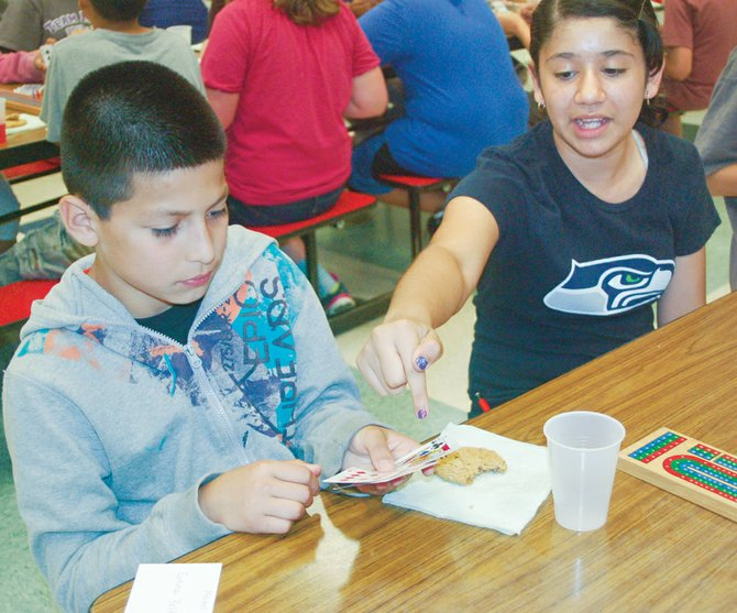 Washington Elementary School cribbage player Perla Flores (R) helps fellow player Noah Rodriguez sort through his cards. The pair are among 78 fourth and fifth graders who took part in the annual Washington Elementary School Cribbage Tournament last Friday.