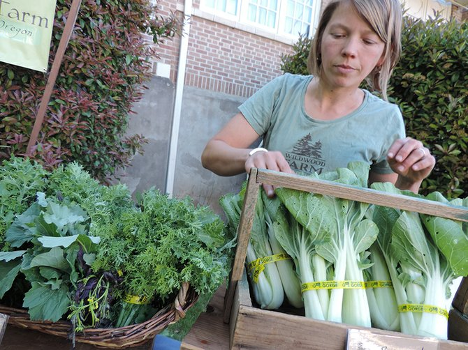 Laurel Bourret of Wildwood Farm sets out fresh bok choy at Hood River Farmers' Market on Thursday at Hood River Middle School.