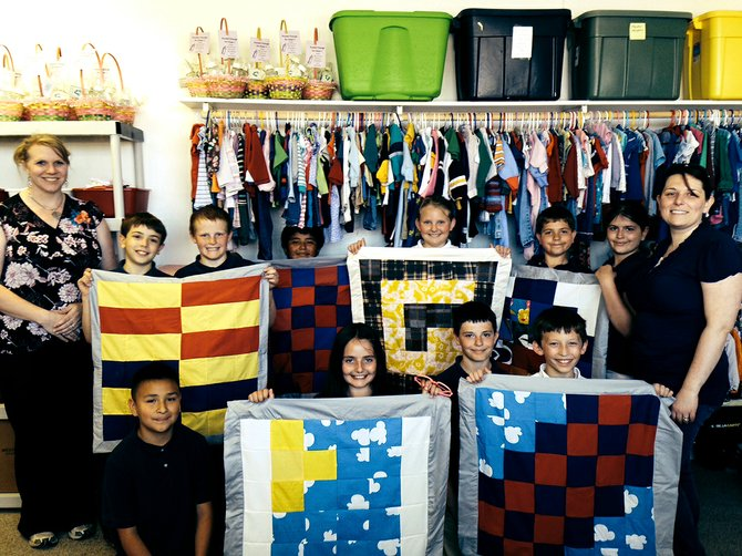 Mrs. Murdock's 3rd and 4th grade class is pictured with the six baby quilts they made.