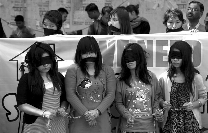 Myanmarese refugee women handcuff, blindfold and cover their mouths with black cloths during a protest on International Women's Day in New Delhi. Myanmarese in Delhi alleged their government used forms of violence against women as weapons of war.
