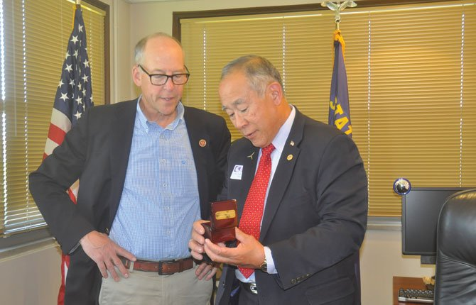 "U.S. REP Greg Walden, left, receives a compass Monday from Dr. Frank Toda, president of Columbia Gorge Community College, that shows geographic '""true north,"" the axis that the earth revolves around. Toda said the gift appropriately represented the Congressman staying the course over more than a decade to obtain funding for the new Fort Dalles Readiness Center, where soldiers train and students study in the field of renewable energy program."