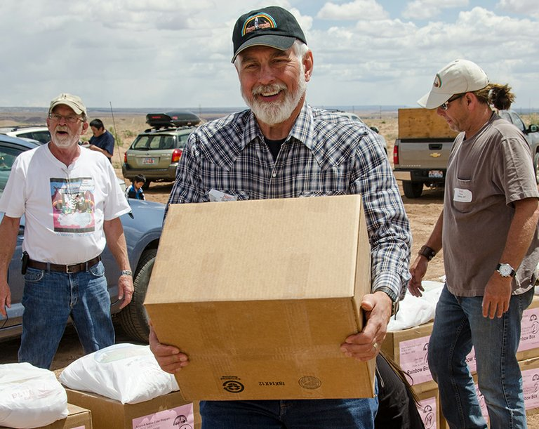 Hood River's Ron Guth joins other Navajo Elder project volunteers in unloading supplies.