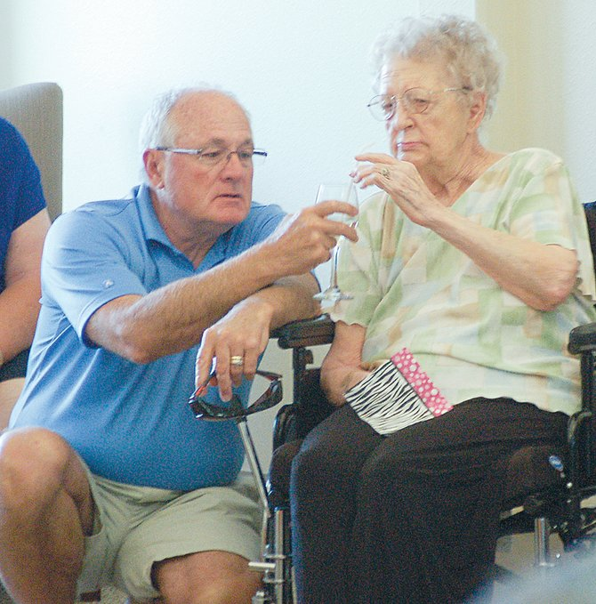 "Local residents, as well as friends and family members of those living at the Sun Terrace retirement center in Sunnyside, are enjoying ""Happy Hour"" socials the last Friday of each month. Here, Chris Powers serves his mother, Vi Powers, a glass of wine at last Friday's gathering. The next ""Happy Hour"" social, open to the public at no cost, is scheduled for Friday, June 27, from 3 to 4 p.m. ""The more the merrier,"" Sun Terrace spokesman Cheryl Larrick said in opening the retirement village to the public for the friendly get-togethers."