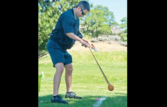 An orange in stretch nylon makes an awkward club for Zack Chown of the Techno Gym Group, one of the teams competing in the 29th Annual Tournament of Tradition Golf Benefit at The Dalles Country Club Tuesday. Proceeds from the tournament will benefit the Breast Health for Strong Families Program, providing free mammograms to local women who qualify.