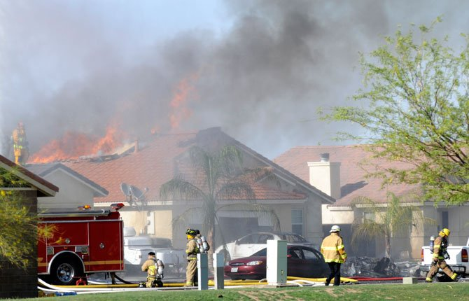 FIREFIGHTERS WORK near houses after a Marine jet crashed in a residential area in the desert community of Imperial, Calif., setting two homes on fire June 4. The pilot ejected safely, and there was no immediate word of any injuries on the ground. The Harrier AV-8B went down at 4:20 p.m. in Imperial, a city of about 15,000 near the U.S.-Mexico border about 90 miles east of San Diego.