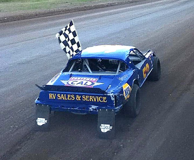 Mike Roberts of Omak drives off with the checkered flag after winning a race at Eagle Track Raceway.