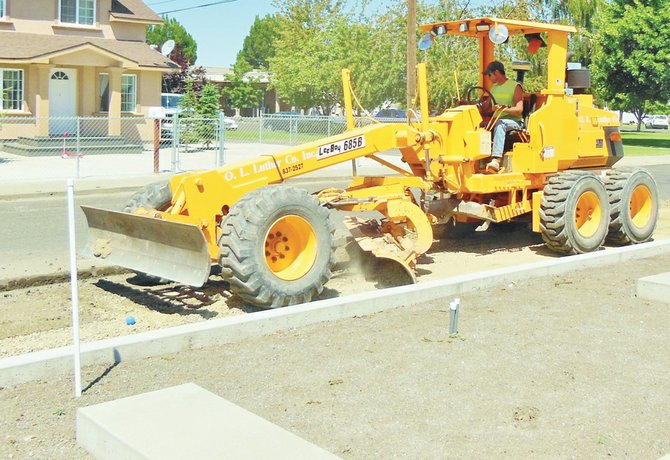 Lee Luther grades the side of Jerry Taylor Veterans Plaza in Sunnyside this past Thursday as work continues on the memorial. With the curbing nearly complete, the asphalt near the memorial is being replaced.