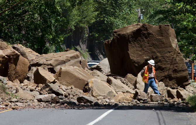 "A worker makes his way through rocks on the Historic Columbia River Highway June 5, east of Portland. State transportation spokesman Don Hamilton said about 1,000 cubic yards of rock and dirt fell Thursday morning, including what he described to The Oregonian as ""one very large rock."" He says the highway will remain closed Thursday and Friday and probably into the weekend."