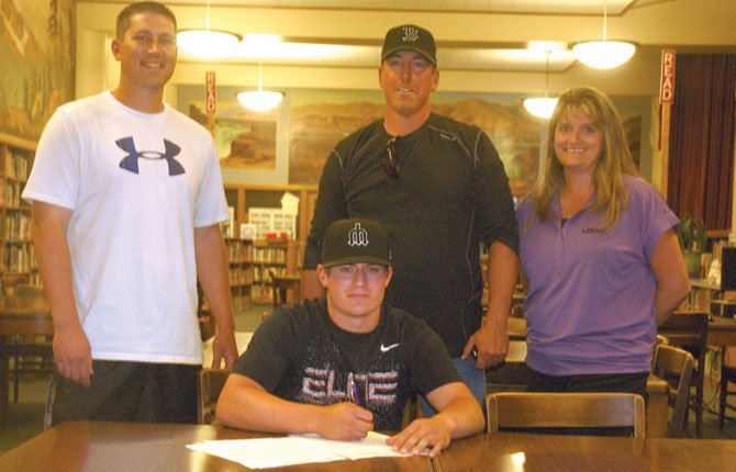 THE DALLES baseball player and former all-state and all-league third baseman Nolan McCall (middle) is surrounded by (from left), head coach J.R. Runyon, father Jeff and mother Cheri while signing scholarship paperwork to play baseball for Bryan Donohue and the Mount Hood Community College Saints.