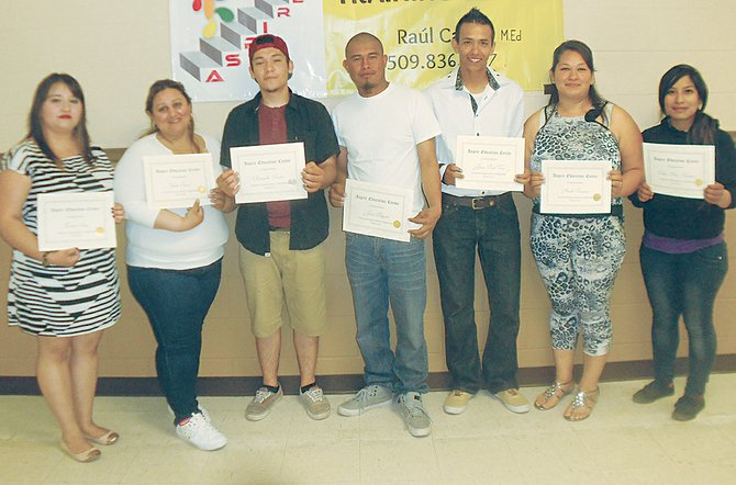 Having just earned their GED, Zvitzen Silva, Yvette Guizar, Christopher Casillas, Jesus Delgado, Paul J. Vera, Anahi Gonzalez and Silva Bello-Tolentino (L-R) proudly show off their certificates.