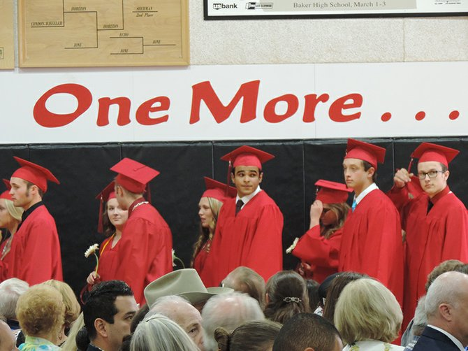 Graduates file past the gymnasium sign that says it all: it was their final act as Horizon Christian School students. From left are Patrick Foss, Jenna Mobley, Kirby Carter, Cheyenne Rosander, Amar Mann, David VanDyke, and Tim Johnson. Also graduating: Kaylee Demchuk, Micah Engel, Nicholas Ficco-Wright, Luke Kempf, Rocky Lemley, Sareh Loredo, Jenna Mobley, Austin Requa, McKenna Roberts, Brooke Serdar, Brent Smith, and Matt Totaro.