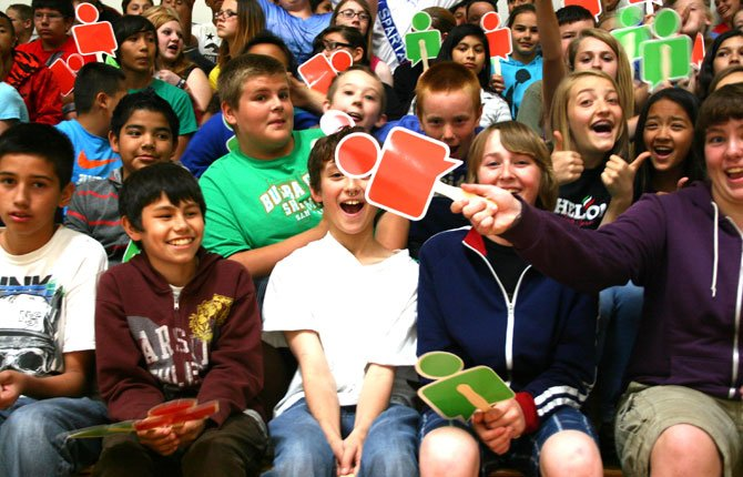 SIXTH GRADERS at the dalles middle school, from left, Julian Aguilar (front row), Boone Cooper (back row), Cylis Johnson (center) and Raven Bierwirth (right) wave paddles representing social media while their classmate Riley Brewer gives a cheerful thumbs up (far right) at Google's Internet Safety Roadshow on June 5.