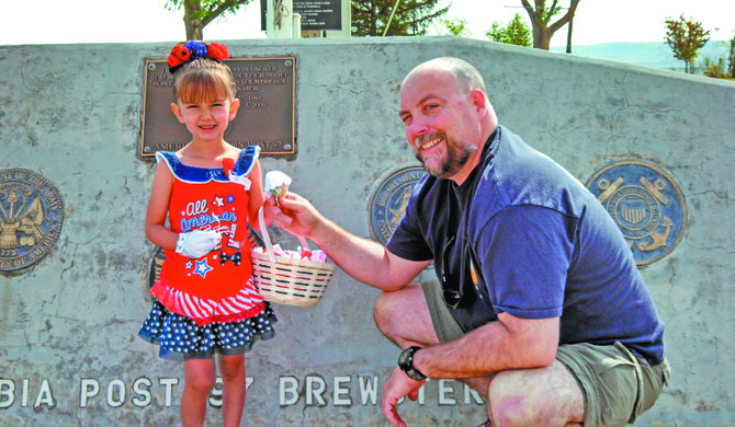Shaylee Todd, 5, of Okanogan, sells the first poppy for Memorial Day to Brewster Mayor Lee Webster on May 16. Todd is this year's poppy girl for American Legion Post 97 in Brewster.