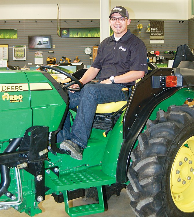 Eric Garza checks out a John Deere tractor at the RDO dealership in Sunnyside. He is a transactional account manager for the dealership, which means he helps farmers get the equipment they need.